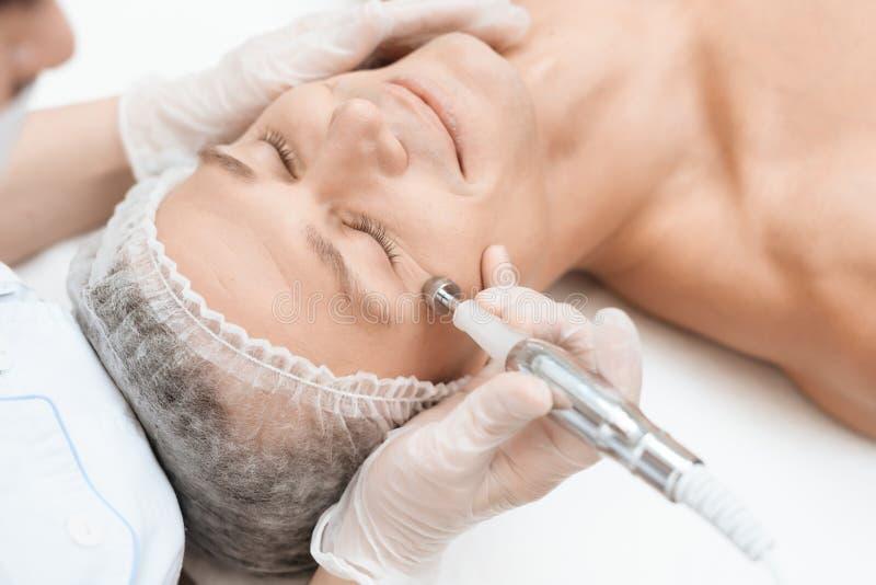 Ein Mann kam zur Laser-Haarabbaugesichtsbehandlung Doktor führt ihn im Gesicht mit einem modernen Laser-epilator lizenzfreie stockfotografie