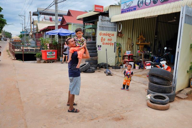 Ein Mann Kambodschas, Siem Reap 12/08/2018 mit einem Kind in seinen Armen nahe dem Reifengeschäft, Elendsviertel von Asien, Bewoh lizenzfreie stockfotografie
