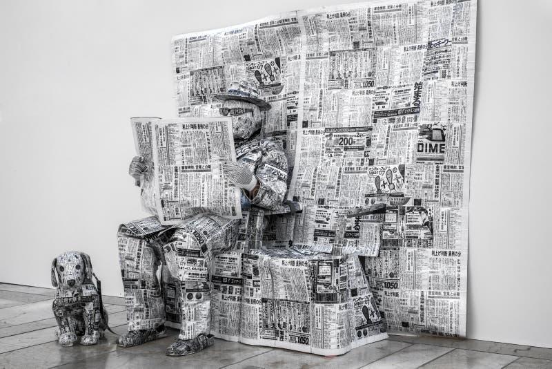 Ein Mann kleidete in den Zeitungen und in seinem Hund an stockbild