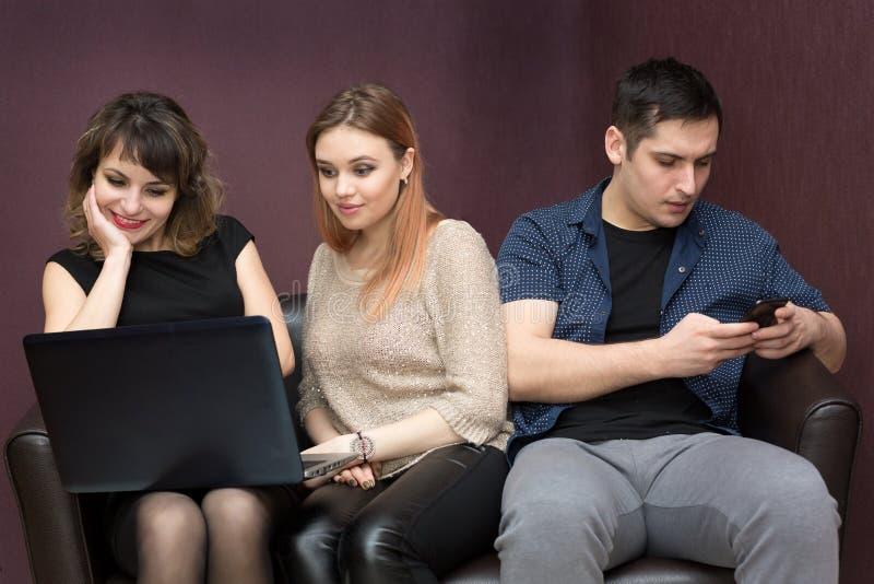 Ein Mann langweilt sich mit zwei Mädchen, die einen Film aufpassen lizenzfreie stockbilder
