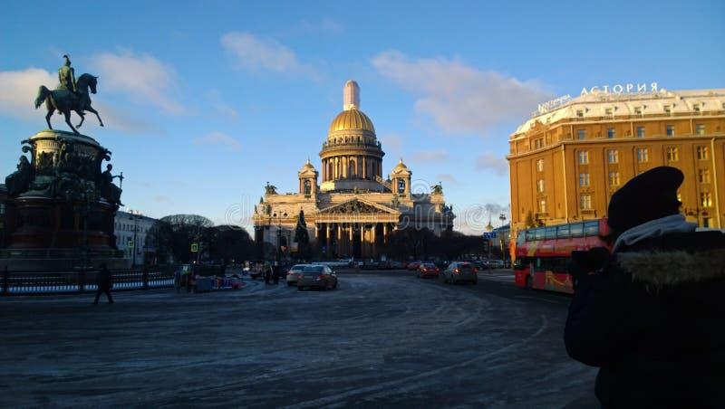 Ein Mann macht ein Foto des Anblicks von St Petersburg: ` S St. Isaac Kathedrale und Monument zu Nicholas das erste an einem sonn lizenzfreies stockfoto