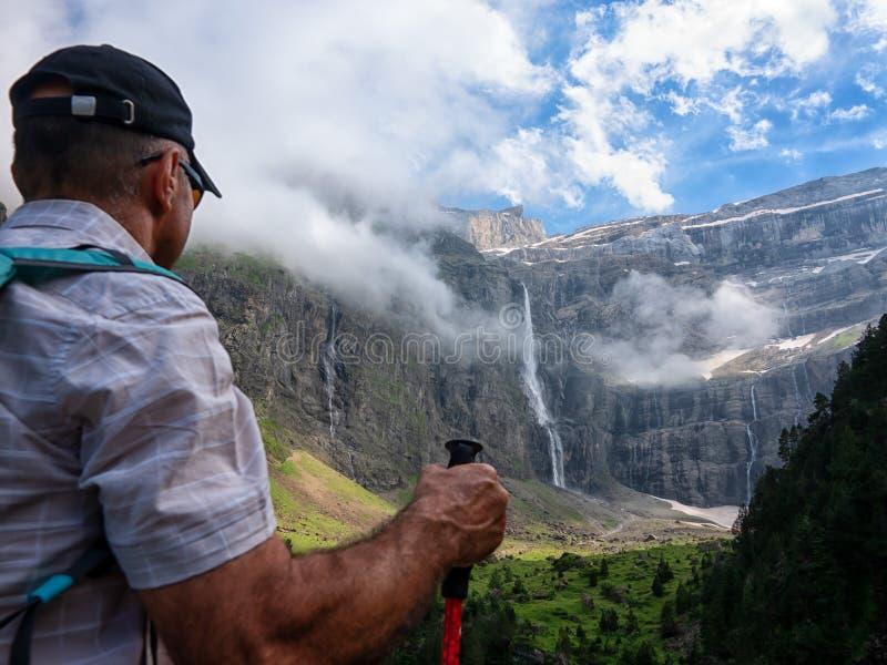 Ein Mann macht eine Wanderung in den Bergen und betrachtet die Spitzen stockbilder