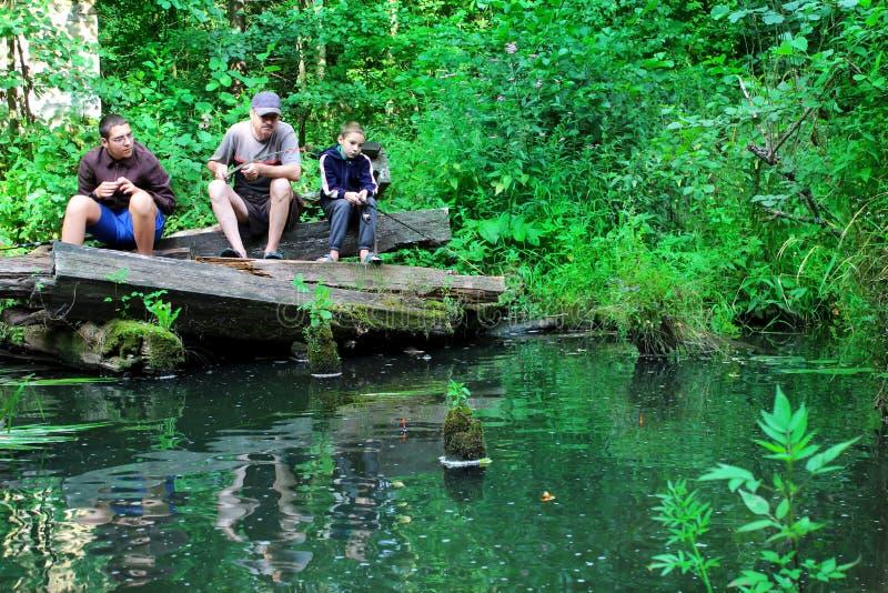 Ein Mann mit den Jungen, die auf ariver fischen stockbild