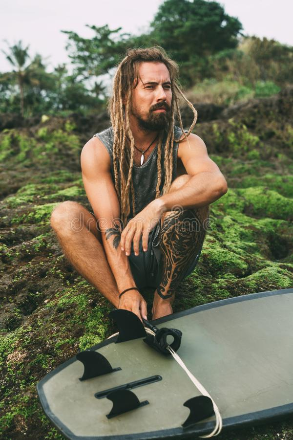 Ein Mann mit Dreadlocks, Tätowierungen und Surfbrett stockbilder