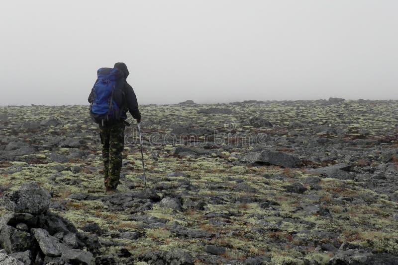 Ein Mann mit einem blauen Rucksack von der Rückseite in den Bergen lizenzfreie stockbilder