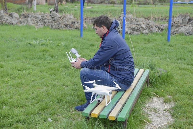 Ein Mann mit einem Fernsteuerungs-quadroopter in seinen Händen sitzt auf einer Bank Weißes quadroopter bereiten sich für Flug vor stockfoto