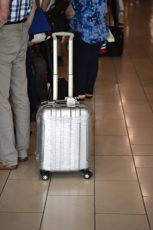 Ein Mann mit einem großen silbernen Koffer auf Rädern in Erwartung des Besteigens des Flugzeugs blurry stockfotografie