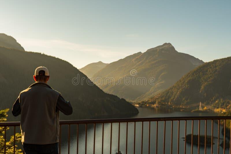 Ein Mann mit einem Hut und einer Weste passt den Sonnenuntergang über Diablo Lake von Vista-Punkt im Nordkaskaden-Nationalpark au lizenzfreie stockfotos