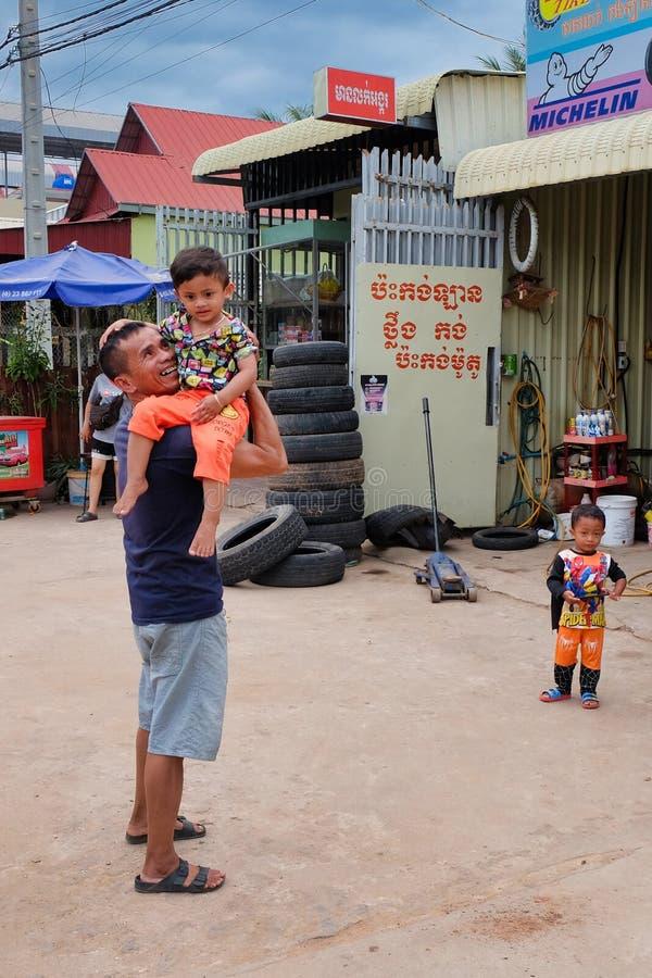 Ein Mann mit einem Kind in seinen Armen nahe dem Reifengesch?ft, Elendsviertel von Asien, Bewohner von schlechten Bereichen von lizenzfreie stockfotos