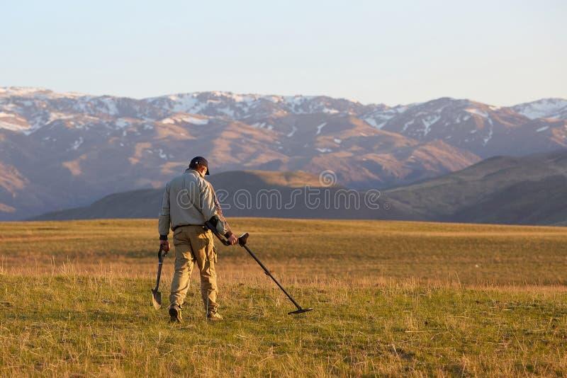 Ein Mann mit einem Metalldetektor auf der Suche nach einem Schatz stockbilder
