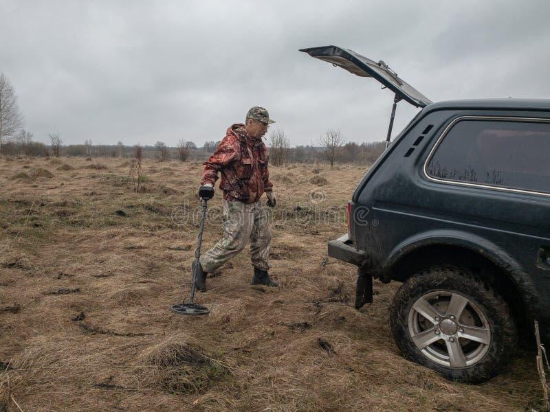 Ein Mann mit einem Metalldetektor sucht alten Münzen, Waffen und nach Schatz lizenzfreies stockfoto
