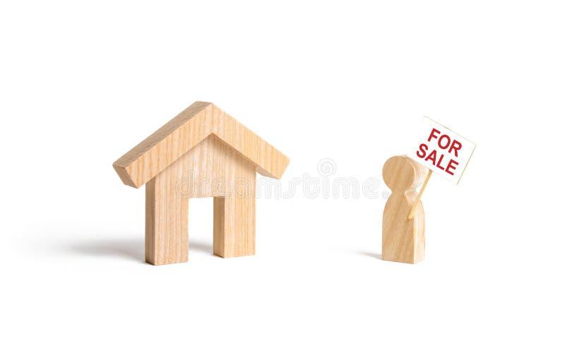 Ein Mann mit einem Plakat für Verkaufsstände nahe dem Haus auf einem lokalisierten Hintergrund Konzept des Verkaufs eines Hauses, lizenzfreies stockfoto