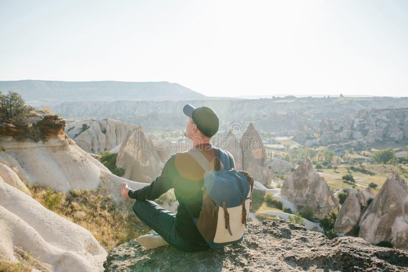 Ein Mann mit einem Rucksack sitzt auf einen Hügel in Cappadocia in der Türkei stockbilder