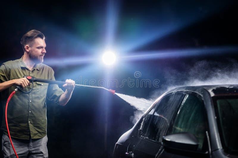 Ein Mann mit einer Bart- oder Autowaschmaschine wäscht ein graues Auto mit einem Hochdruckapparat nachts in einer Waschanlage stockbilder