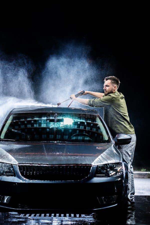 Ein Mann mit einer Bart- oder Autowaschmaschine wäscht ein graues Auto mit einer Hochdruckwaschmaschine nachts herein auf der Str stockbild
