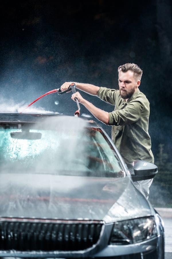 Ein Mann mit einer Bart- oder Autowaschmaschine wäscht ein graues Auto mit einer Hochdruckwaschmaschine nachts herein auf der Str lizenzfreie stockbilder