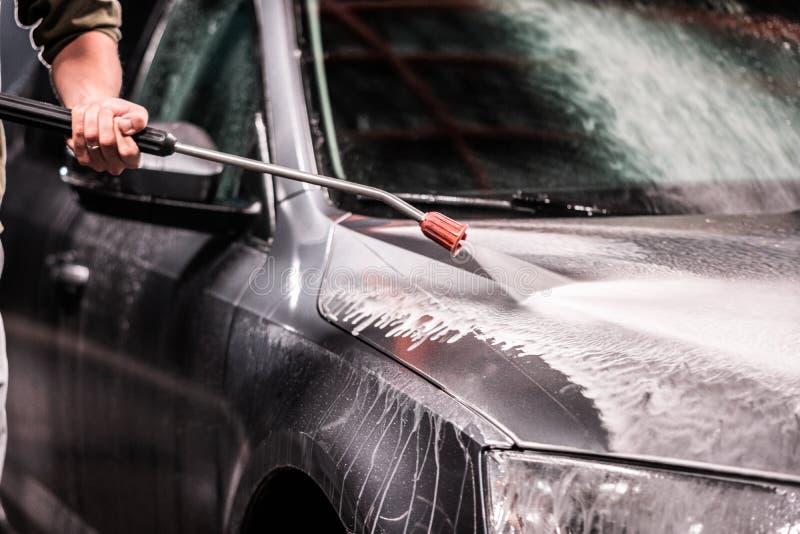 Ein Mann mit einer Bart- oder Autowaschmaschine wäscht ein graues Auto mit einer Hochdruckwaschmaschine nachts in einer Shopwäsch stockbild