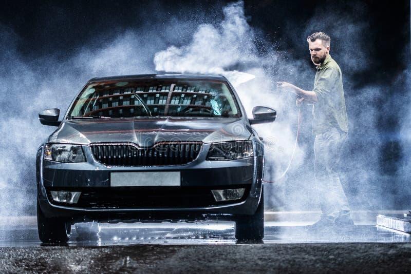 Ein Mann mit einer Bart- oder Autowaschmaschine wäscht ein graues Auto mit einer Hochdruckwaschmaschine nachts in einer Shopwäsch lizenzfreie stockbilder