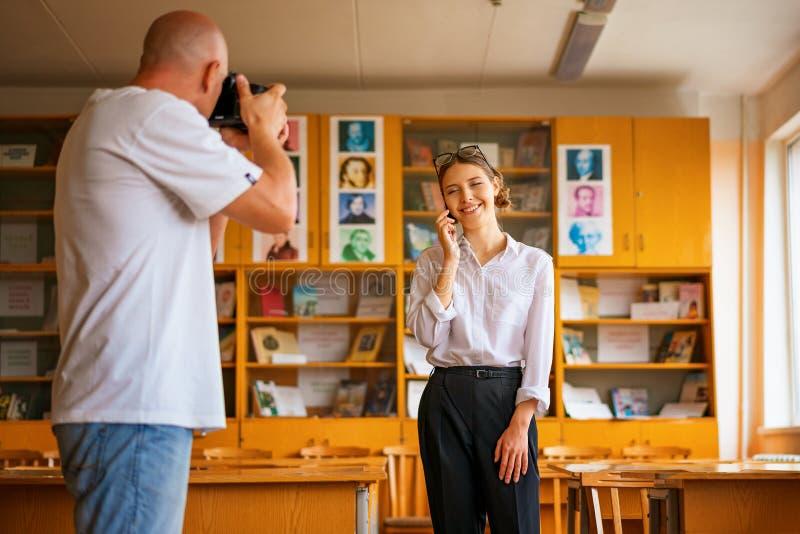 Ein Mann mit einer Kamera, die Fotos eines Mädchens, eine Berufsfotoaufnahme macht stockfotos