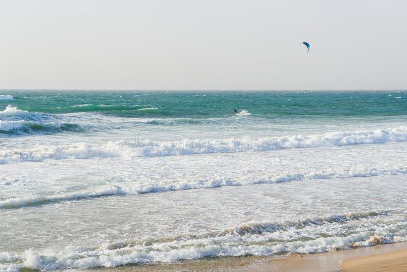 Ein Mann mit Fallschirmfahrten auf ein Surfbrett auf großen Wellen im Meer oder im Ozean lizenzfreie stockfotos