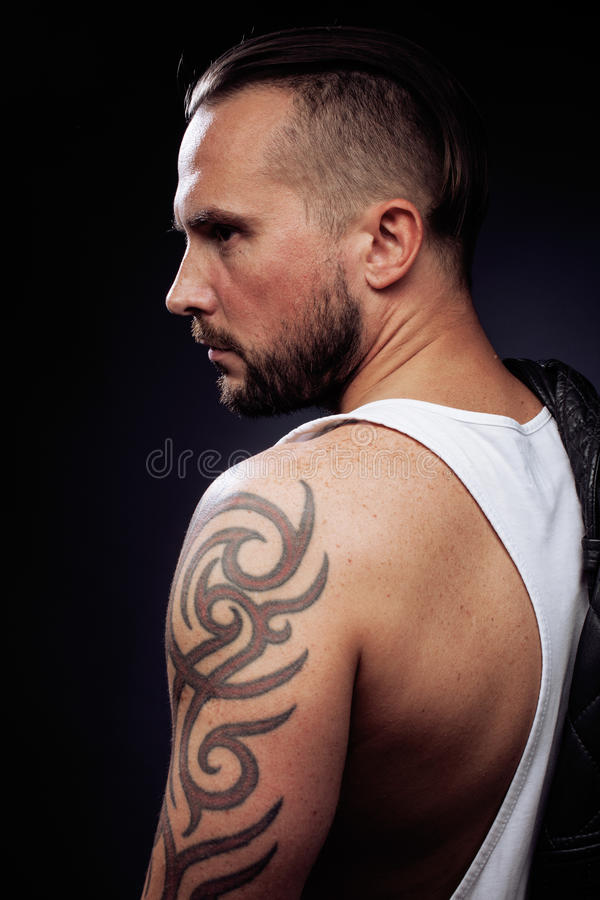 Ein Mann mit Tätowierungen auf seinen Armen Schattenbild des muskulösen Körpers kaukasischer grober Hippie-Kerl mit dem modernen  stockfoto