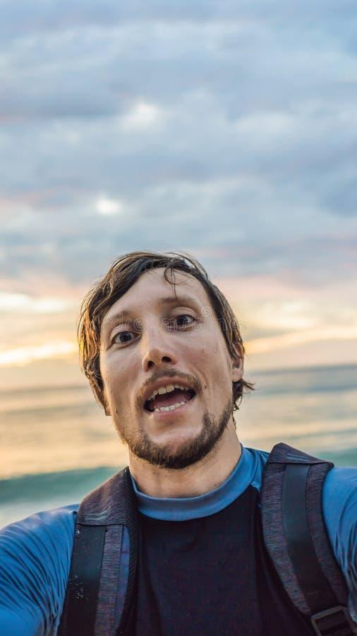 Ein Mann nimmt ein selfie auf dem Hintergrund des Meer- und Sonnenuntergang VERTIKALEN FORMATS für bewegliche Geschichte Instagra lizenzfreie stockbilder