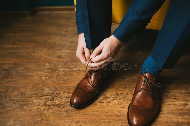 Ein Mann oder ein Bräutigam in einem blauen Anzug bindet oben Spitzee auf braunen Lederschuhe Brogues auf einem hölzernen Parkett stockbilder