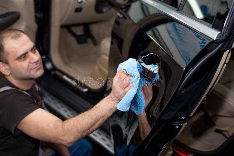 Ein Mann poliert ein schwarzes Auto lizenzfreie stockfotografie