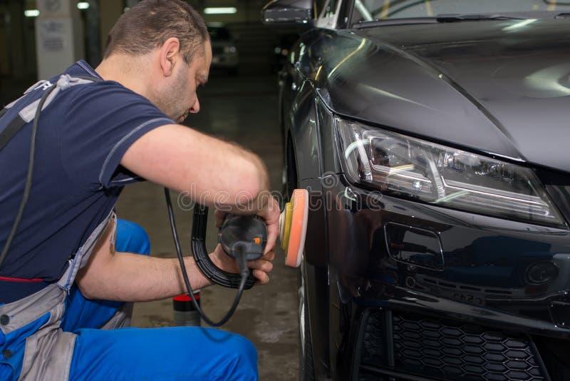 Ein Mann poliert ein schwarzes Auto stockfoto