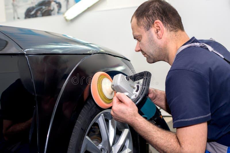 Ein Mann poliert ein schwarzes Auto stockbild