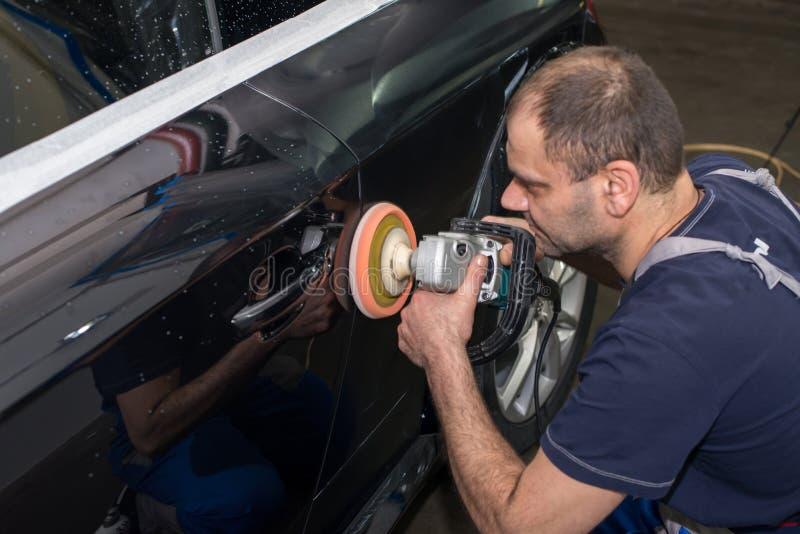 Ein Mann poliert ein schwarzes Auto stockfotos