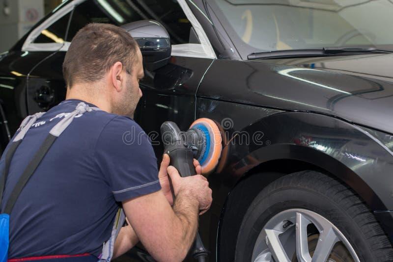 Ein Mann poliert ein schwarzes Auto lizenzfreie stockbilder