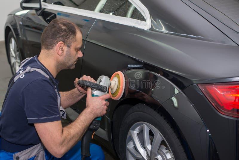 Ein Mann poliert ein schwarzes Auto stockbilder