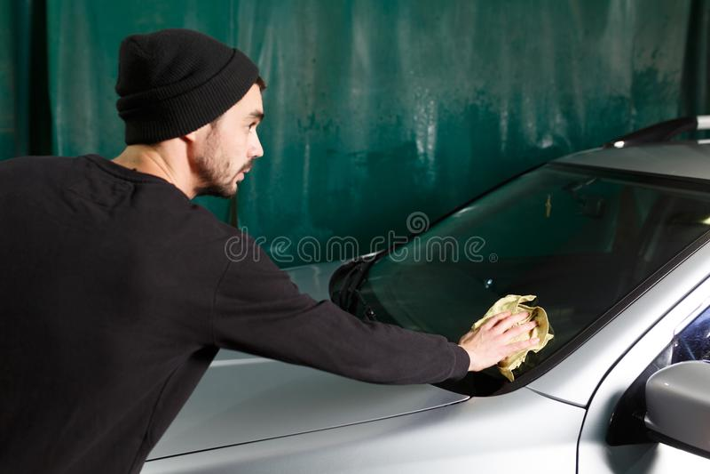 Ein Mann poliert ein vorderes Glas lizenzfreies stockbild