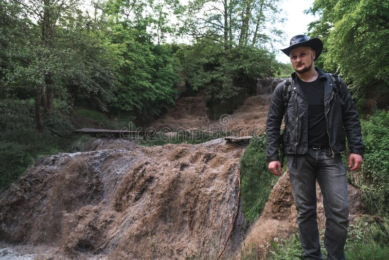 Ein Mann, ein Reisender in einer Lederjacke und ein Cowboyhut Großer voll-flüssiger Wasserfall mit Schmutzwasser, eine Reise, ein stockbild