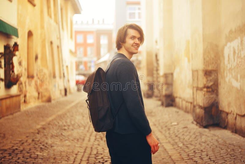Ein Mann reist in Europa Ein Mann lächelt, geht durch die Straßen der alten Stadt, mit einem Aktenkoffer stockfotografie