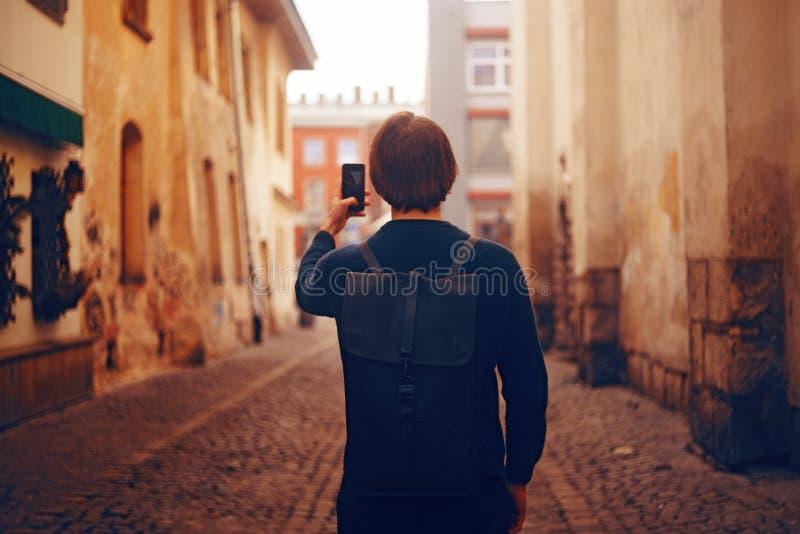 Ein Mann reist in Europa-Straße Ein Mann lächelt, geht durch die Straßen der alten Stadt, mit einem Aktenkoffer Studentenreisen a lizenzfreie stockfotos