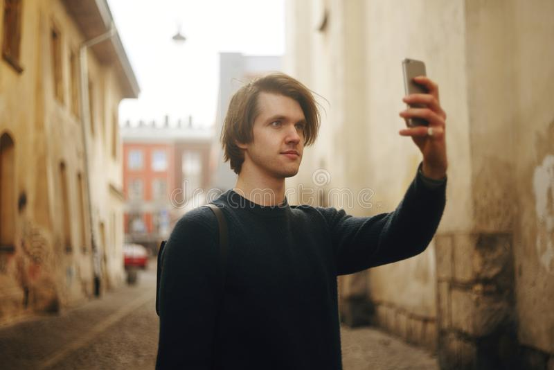 Ein Mann reist in Europa-Straße Ein Mann lächelt, geht durch die Straßen der alten Stadt, mit einem Aktenkoffer Studentenreisen a stockfoto