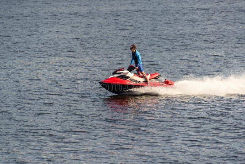 Ein Mann reitet einen roten Jet-Ski auf den Fluss stockbild