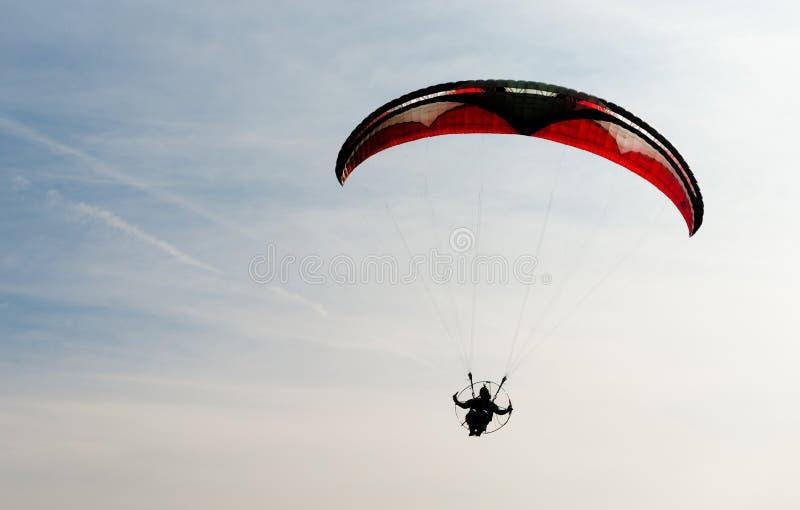 Ein Mann reitet Fliegen-Ultralight Fliegen durch blauen Himmel stockfotos