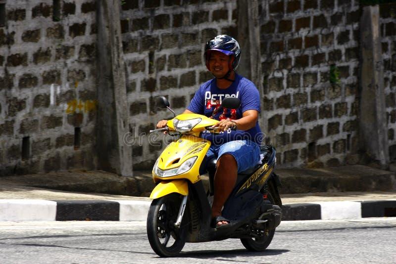 Ein Mann reitet seinen Roller auf eine ansteigende Straße in Antipolo-Stadt stockfoto