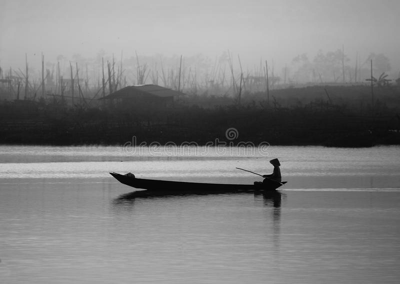 Ein Mann-Ruderboot in einem nebelhaften See lizenzfreies stockfoto