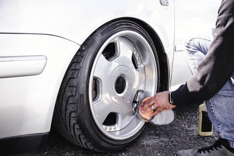 Ein Mann säubert und poliert die Räder seines Autos Fallengelassenes weißes Auto auf Luftsuspendierung lizenzfreies stockbild