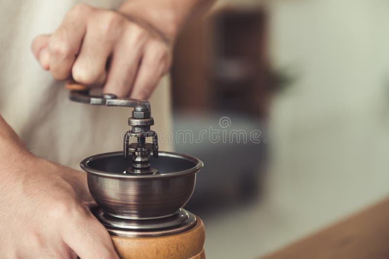 Ein Mann ` s Hände unter Verwendung der hölzernen Kaffeemühle der Weinlese zum Mahlen von Kaffeebohnen stockfoto