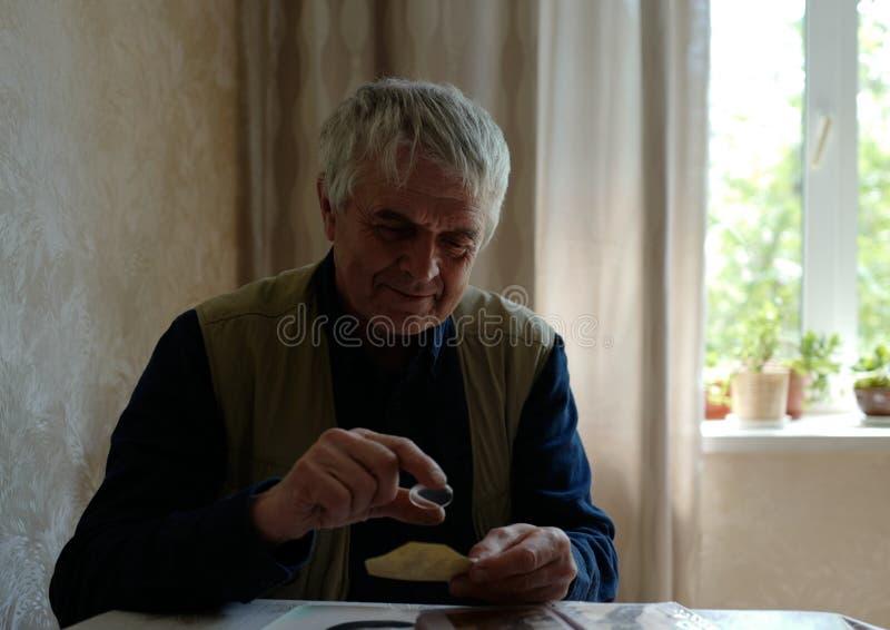 Ein Mann schaut durch ein altes Dokument der Lupe lizenzfreie stockfotografie