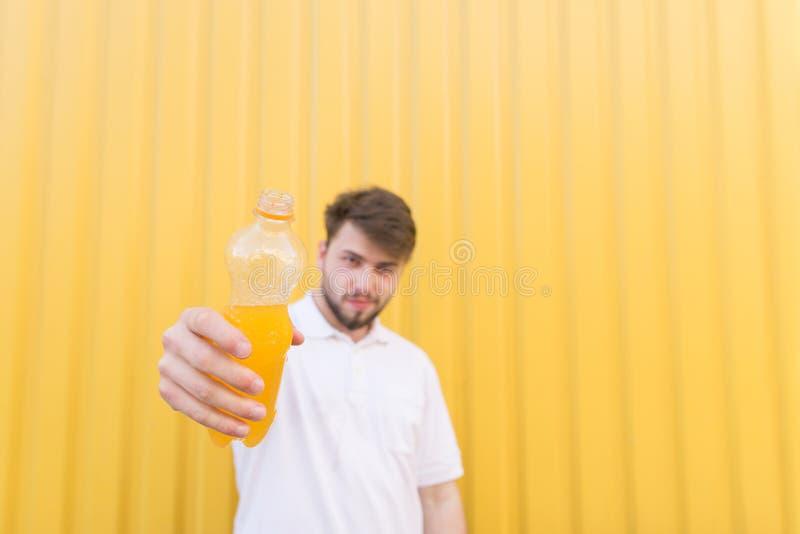 Ein Mann schickt eine Flasche seiner Hand zur Kamera Ein Mann bietet eine Flasche des Orangensaftgetränkes an stockbild