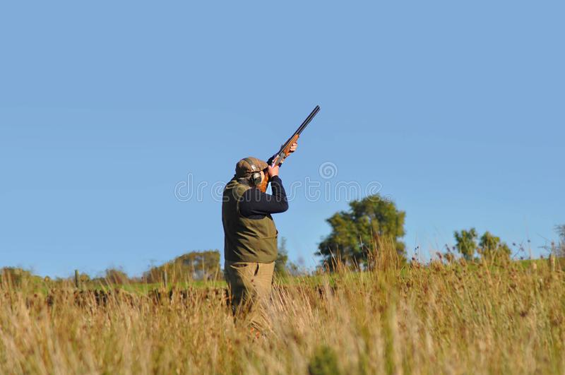 Ein Mann schie?ende Enten mit Hintergrund des blauen Himmels f?r Textkopie stockbild