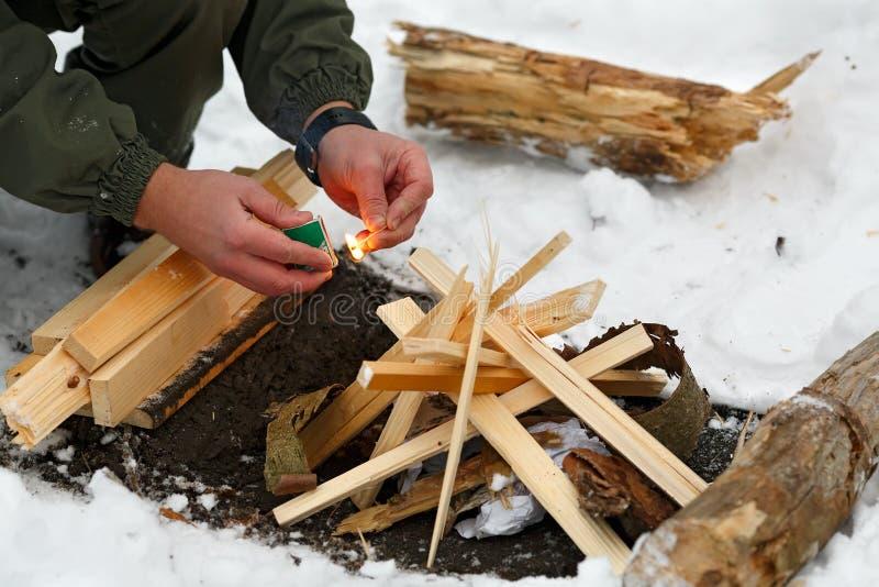 Ein Mann schlägt ein Match, um ein Feuer zu machen stockbild