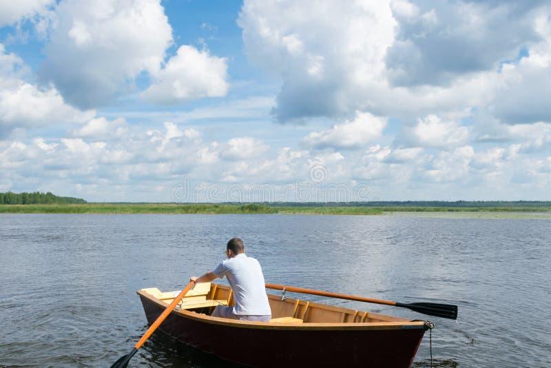 Ein Mann schwimmt auf ein hölzernes Boot auf dem See auf einem netten sonniger Tagesabschluß oben, aktives Wochenende lizenzfreies stockfoto
