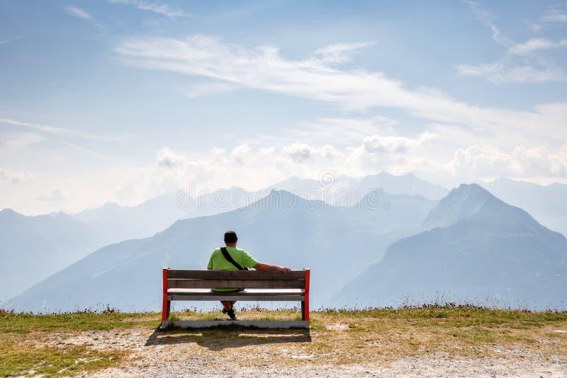 Ein Mann sitzt auf einer Holzbank an der Spitze der Alpen und Blicken in der schönen Berglandschaft stockbilder